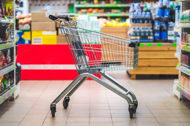 Carrinho de compras no corredor do supermercado. compra de comida no supermercado. Foto Premium