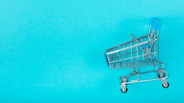 Carrinho de compras no fundo liso Foto gratuita