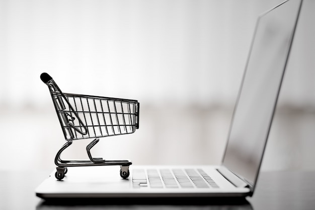 Carrinho de compras no laptop, compras on-line e conceito de serviço de entrega. Foto Premium