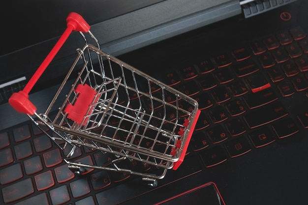 Carrinho de compras on-line no teclado preto. trole vermelho mettal em um teclado de laptop. serviço de compras na web online. oferece entrega em domicílio. copyspace para texto. Foto Premium