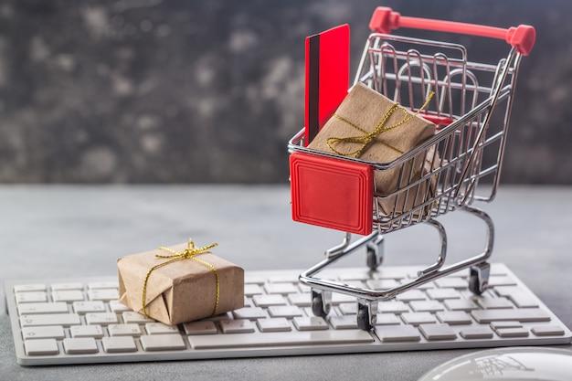 Carrinho de compras pequeno com presentes e cartão de crédito em um conceitos de teclado de laptop Foto Premium
