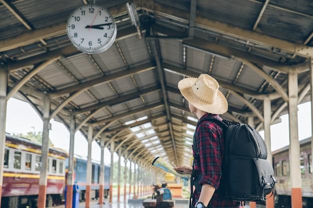 Carrinho de mochileiro sob o relógio no feriado de viagens de trem estação turistas. viagens concept.man viajar Foto Premium