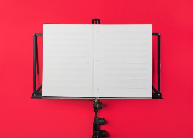 Carrinho de música com página musical branca em branco sobre fundo vermelho Foto gratuita