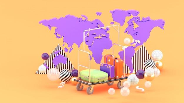 Carrinho de paquete entre o mapa do mundo e bolas coloridas na laranja. renderização em 3d. Foto Premium