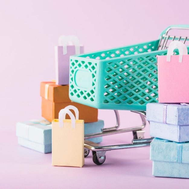 Carrinho de supermercado com caixas de presente colorido Foto gratuita