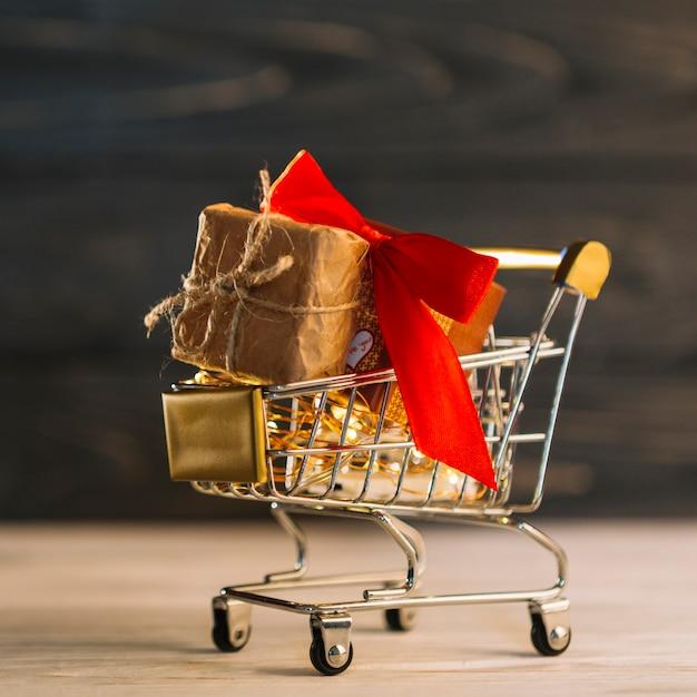 Carrinho de supermercado pequeno com caixa de presente com faixa vermelha Foto gratuita