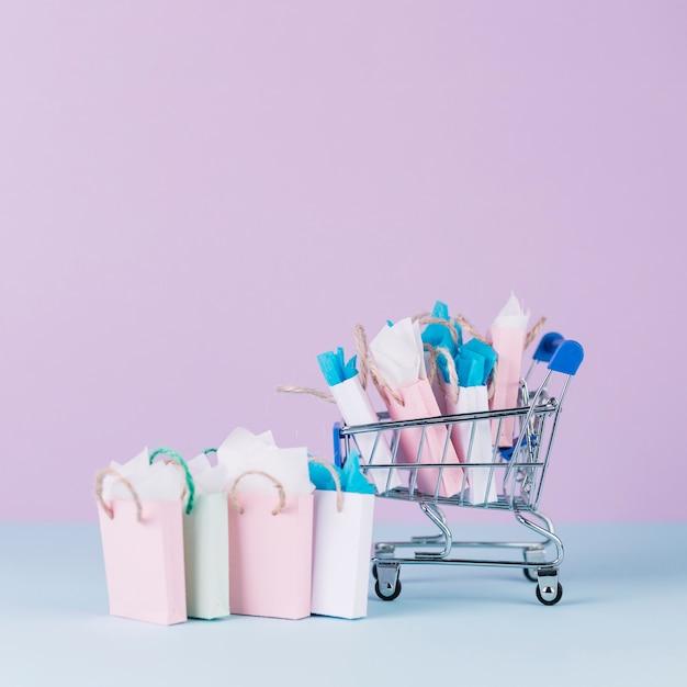 Carrinho em miniatura, cheio de sacolas de papel na frente de fundo rosa Foto gratuita