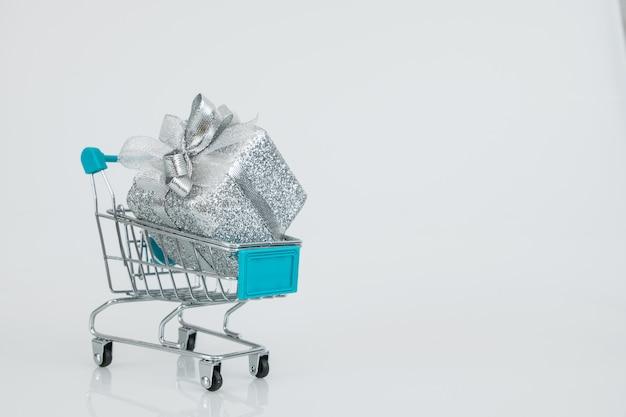 Carrinhos de compras com a caixa de presente totalmente caber em carrinhos, compra on-line e-commerce. Foto Premium