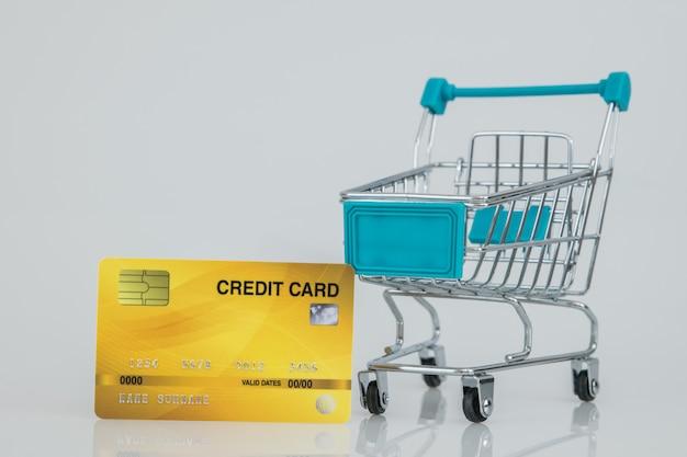 Carrinhos de compras com o cartão de crédito amarelo, compra on-line e-commerce. Foto Premium