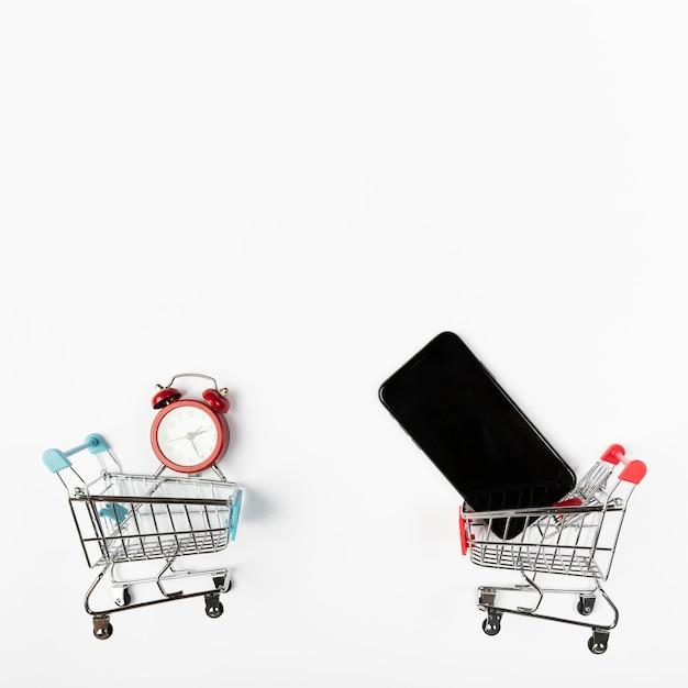 Carrinhos de compras com telefone e despertador Foto gratuita