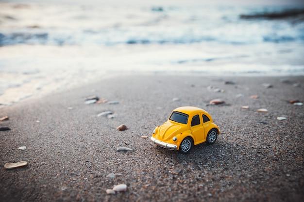 Carro amarelo do brinquedo na praia na luz solar no verão. Foto Premium