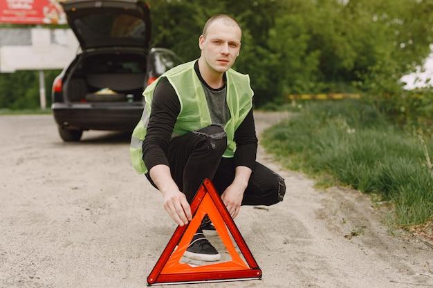 Carro com problemas e um triângulo vermelho para avisar outros usuários da estrada Foto gratuita