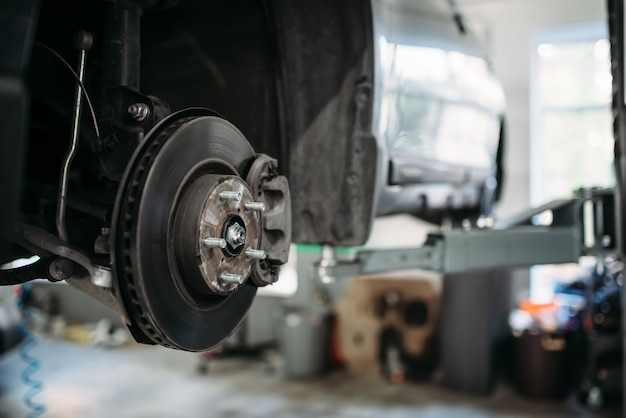 Carro com roda removida no elevador, disco de freio. Foto Premium