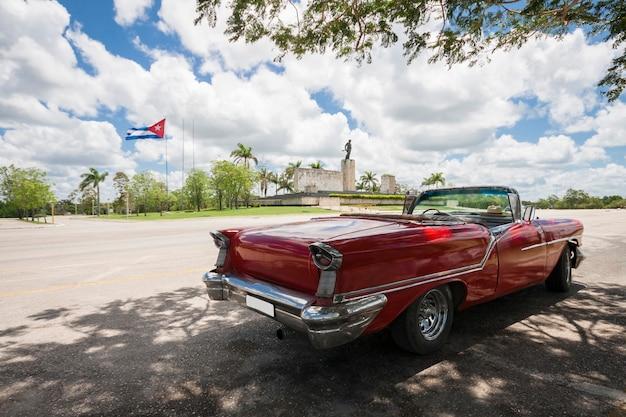 Carro conversível clássico com monumento e bandeira cubana no fundo Foto gratuita