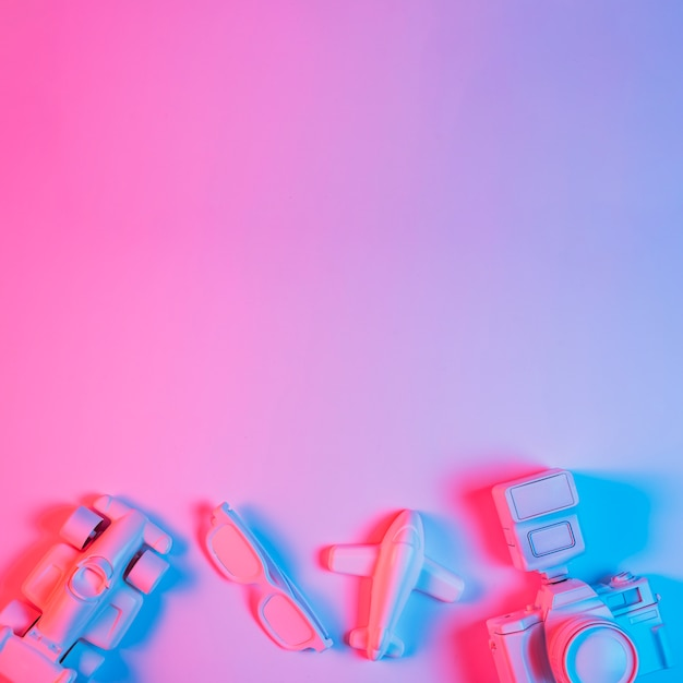 Carro de brinquedo; avião; espetáculo e câmera disposta na parte inferior do fundo rosa com luz azul Foto gratuita