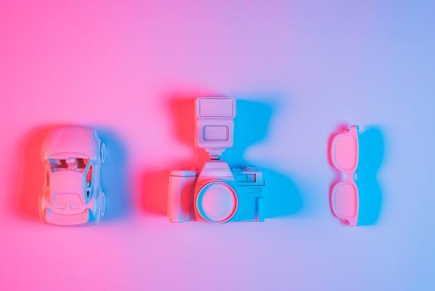 Carro de brinquedo; câmera retro e espetáculo organizado em uma linha no pano de fundo rosa com efeito de luz azul Foto gratuita