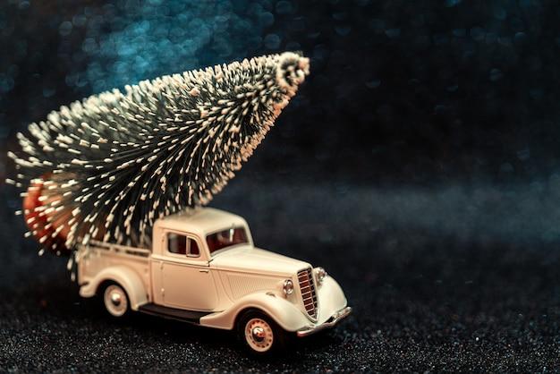 Carro de brinquedo carrega árvore de natal para férias Foto Premium