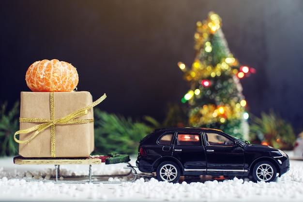 Carro de brinquedo carrega um presente para o natal e ano novo Foto Premium