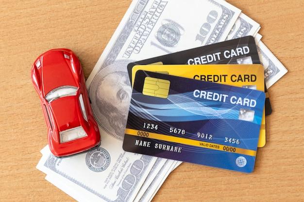 Carro de brinquedo, cartões de crédito e dólares na mesa de madeira. reembolso de dinheiro e conceito financeiro Foto Premium