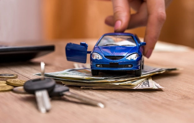 Carro de brinquedo, chaves e dinheiro na mesa Foto Premium