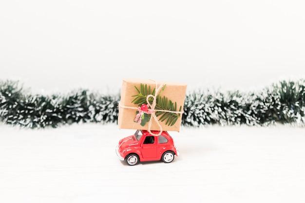 Carro de brinquedo com caixa de presente perto ouropel Foto gratuita
