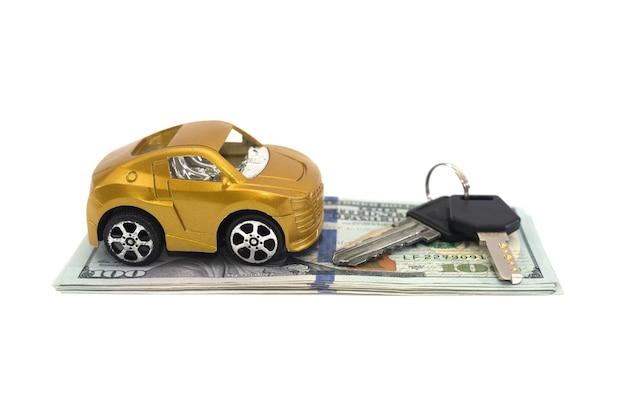 Carro de brinquedo, dólares e chaves isolados no fundo branco. conceito de compra de automóveis. Foto Premium