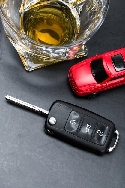Carro de brinquedo e vidro de acidente de acidente de metáfora de uísque isolado no branco Foto Premium