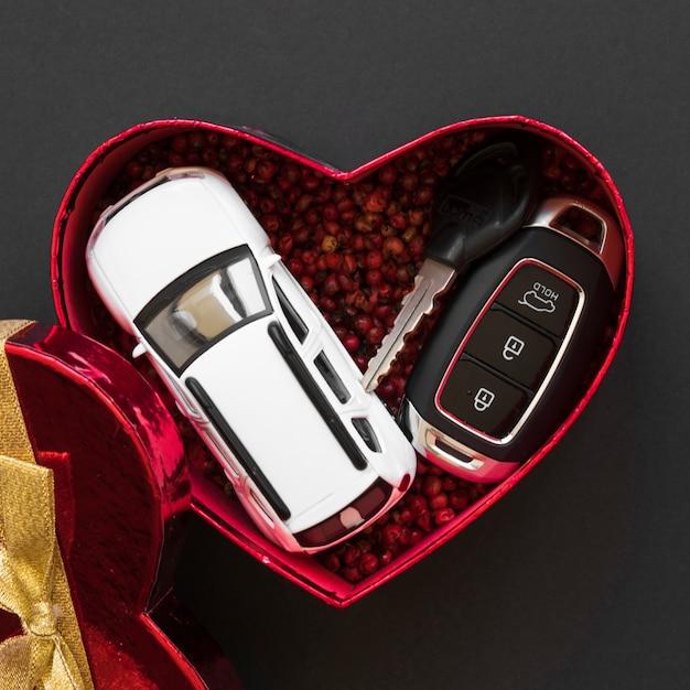 Carro de brinquedo perto de chaves de alarme na caixa de presente Foto gratuita