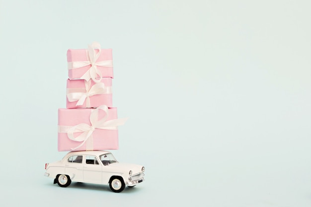 Carro de brinquedo retrô branco com presentes rosa Foto Premium
