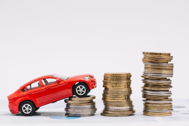 Carro de brinquedo subindo na pilha crescente de moedas contra o fundo branco Foto gratuita