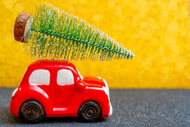 Carro de brinquedo vermelho carrega uma árvore de natal para o feriado. Foto Premium