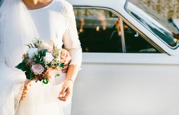 Carro de casamento com flores e noiva com buquê de flores na mão Foto Premium