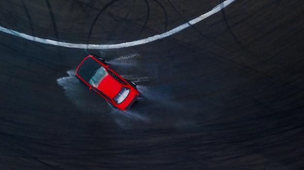 Carro de derivação do motorista profissional aéreo da vista superior na trilha de raça molhada, com respingo da água, carro vermelho. Foto Premium