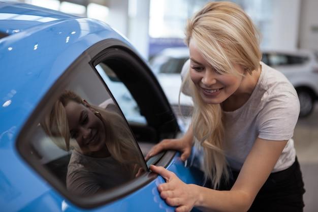 Carro de exame de mulher bonita de cabelos compridos à venda no showroom da concessionária. Foto Premium