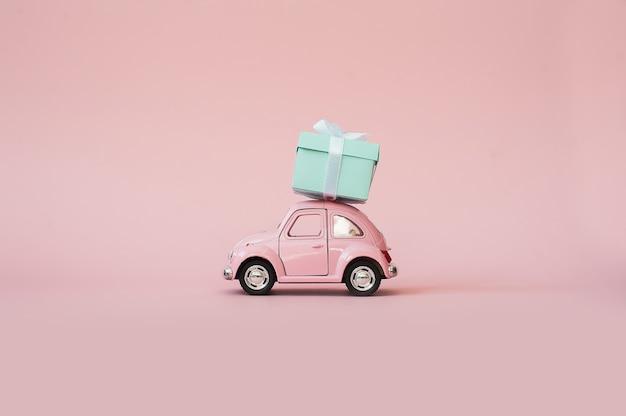 Carro de modelo retrô de brinquedo rosa entregando a caixa de presente em fundo rosa Foto Premium