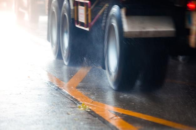 Carro de movimento na grande poça de chuva com água salpicando das rodas Foto Premium