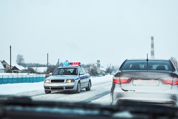 Carro de polícia com luzes vermelhas e azuis parou o carro na estrada de inverno nevado Foto Premium