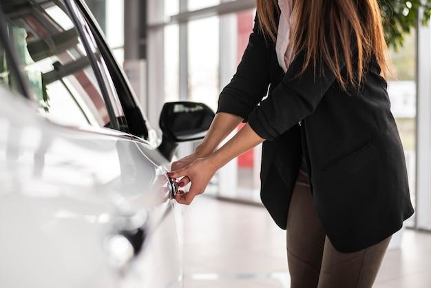 Carro de teste de mulher na concessionária Foto gratuita