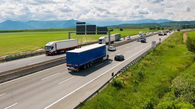 Carro e caminhões que apressam-se na estrada múltipla da pista no desvio de turin, itália. Foto Premium