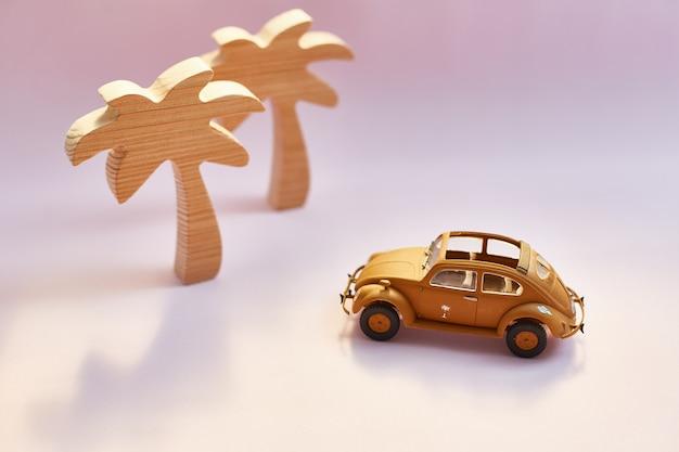 Carro e palmeiras retros amarelos do brinquedo do cabriolet em um fundo cor-de-rosa. Foto Premium