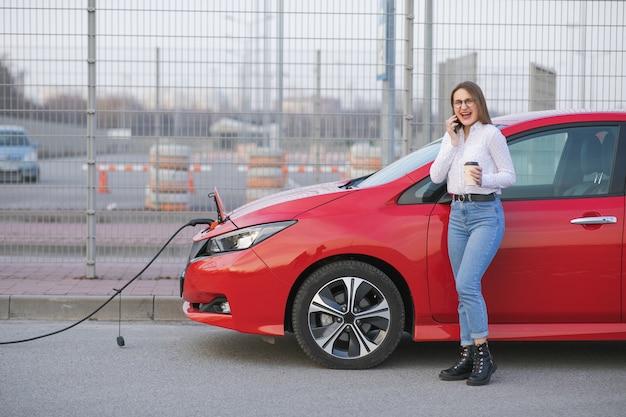 Carro ecológico conectado e baterias de carregamento. garota use café enquanto estiver usando o smartphone e a fonte de alimentação em espera. conecte-se a veículos elétricos para carregar a bateria no carro. Foto Premium