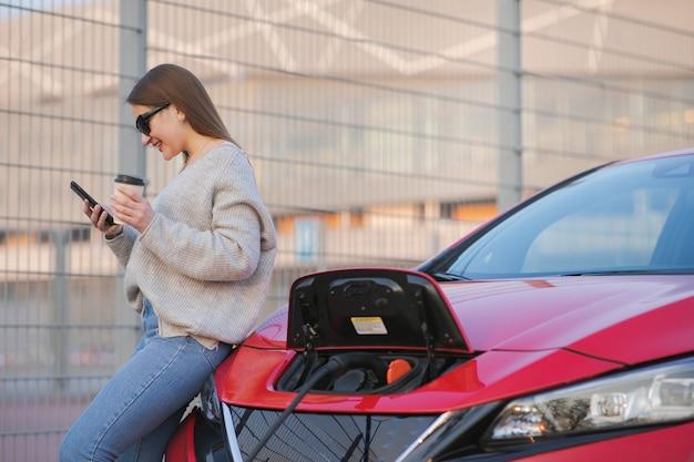 Carro elétrico cobrando na rua. carro ecológico conectado e baterias de carregamento. garota use café enquanto usa o smartphone e aguarda a fonte de alimentação conecte-se a veículos elétricos para carregar Foto Premium