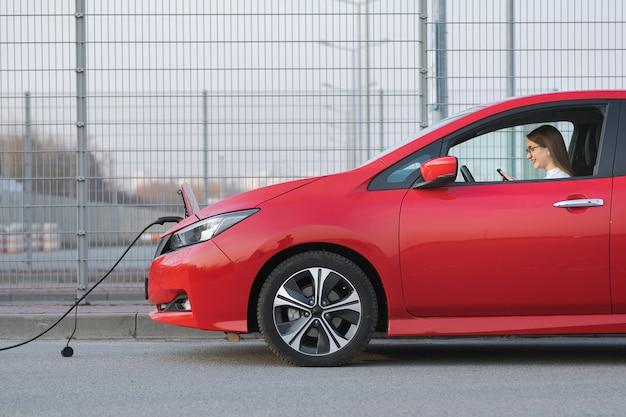 Carro elétrico cobrando na rua. menina caucasiana, usando telefone inteligente e fonte de alimentação à espera de conectar-se a veículos elétricos para carregar a bateria no carro. Foto Premium