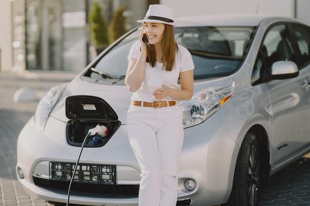 Carro elétrico de carregamento de mulher no posto de gasolina elétrico Foto gratuita