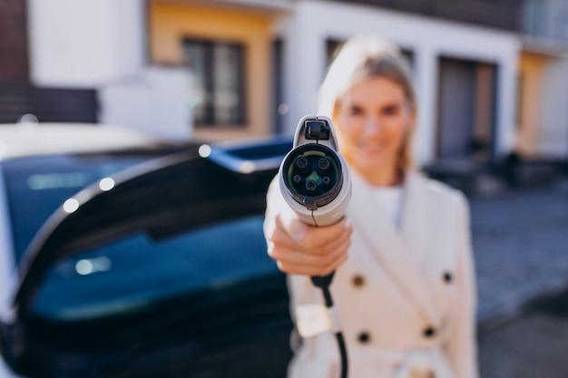 Carro elétrico de carregamento de mulher por sua casa e segurando o carregador Foto gratuita