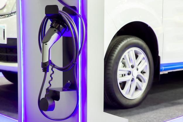 Carro elétrico que carrega no estacionamento com estação de carregamento do carro elétrico na rua da cidade. Foto Premium