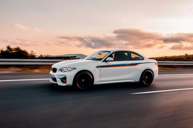 Carro esporte branco com listras de ajuste automático na estrada. Foto gratuita