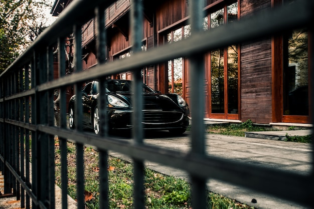 Carro esporte sedan, cor preta em pé na frente de um edifício, vista frontal através de um daqui. Foto gratuita