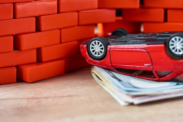 Carro invertido na pilha de contas de um dólar. conceito de seguro de carro, danos depois do acidente Foto Premium