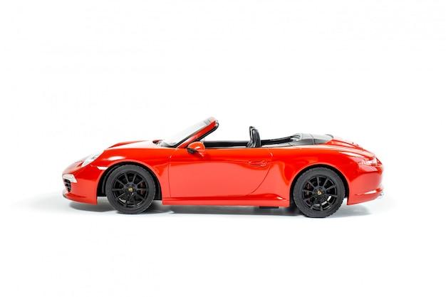Carro modelo vermelho do brinquedo isolado no fundo branco. vista lateral. foco suave. Foto Premium